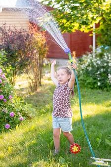 Klein tuinmanmeisje, zij geeft bloemen op het gazon water