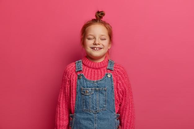 Klein vijfjarig meisje met gember haarbroodje en twee uitstekende tanden, draagt een warme gebreide trui en denim sarafan, lacht van vreugde, houdt de ogen gesloten, kijkt naar grappige cartoon, geïsoleerd op roze muur