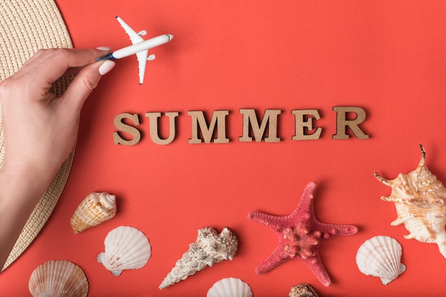 Klein vliegtuig in vrouwelijke hand. word zomer van houten letters. schelpen, zeesterren en een levende koraalruimte. vakantie concept