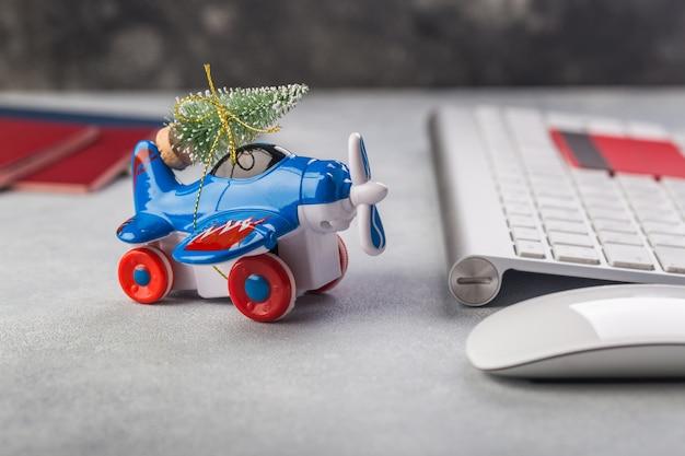Klein vliegtuig met kerstboom, paspoorten, keybaord, creditcard op grijs