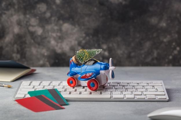 Klein vliegtuig met kerstboom, paspoorten, toetsenbord, creditcardvakantie