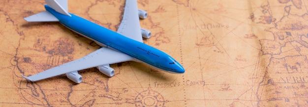 Klein vliegtuig op de kaart voor het plannen van een vakantiereis en accessoires voor op reis