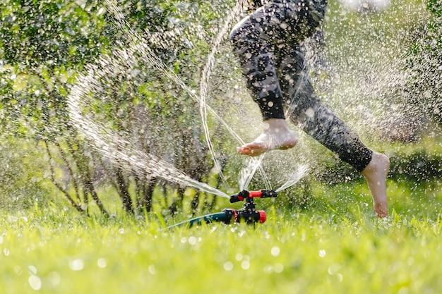 Klein vrolijk kind dat in de tuin speelt met gazons die automatisch water geven