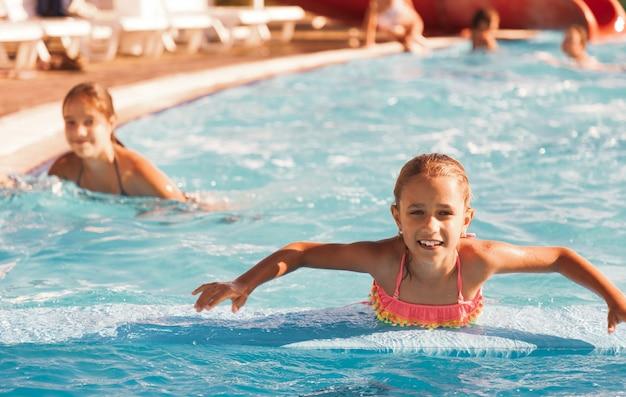 Klein vrolijk meisje dat in het zwembad speelt met helder en helder water en er glimlachend uitziet