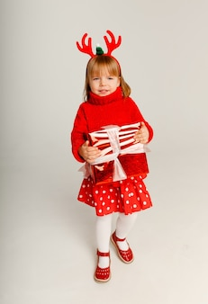 Klein vrolijk meisje in een rode trui heeft een rode geschenkdoos op een witte achtergrond.