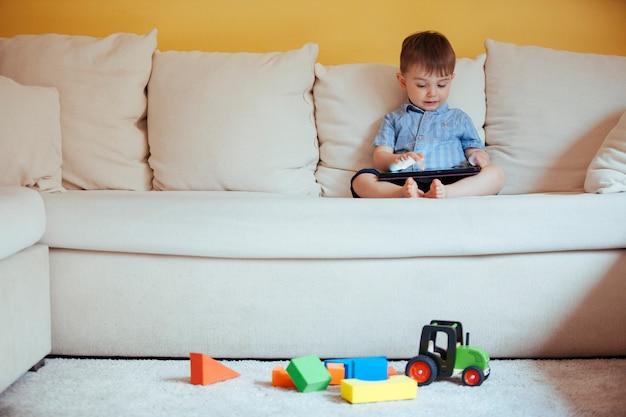 Klein weinig babyjongen die alleen op een het schermapparaat letten speelend met technologie in plaats van educatief speelgoed thuis.