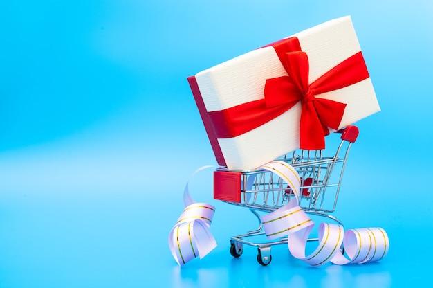 Klein winkelwagentje met grote geschenkdoos binnen op blauwe achtergrond.