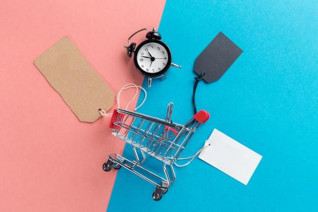 Klein winkelwagentje met wekker. winkelen tijd concept