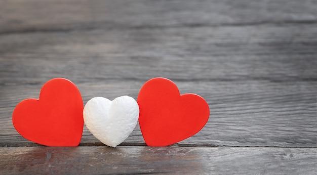 Klein wit hart en twee rode harten op een houten achtergrond. familie concept