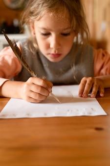 Klein zevenjarig meisje tekent een verdwijnende tekening op papier met een echte geslepen eendenpen met melk in plaats van inkt