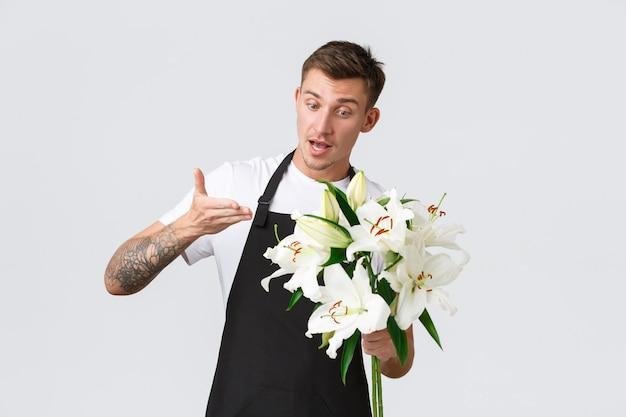 Kleinbedrijf retail en werknemers concept charismatische knappe bloemist verkoper in bloemenwinkel sel...