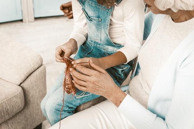 Kleindochter die haar grootmoeder laat zien wat ze heeft leren breien.