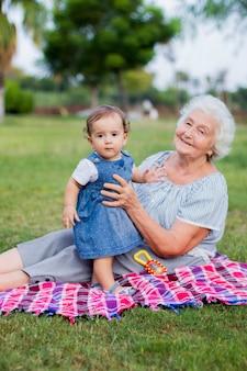 Kleindochter en grootmoeder omhelzen elkaar en wandelen in het herfstpark