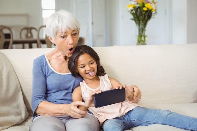 Kleindochter en grootmoeder selfie te nemen op de mobiele telefoon in de woonkamer