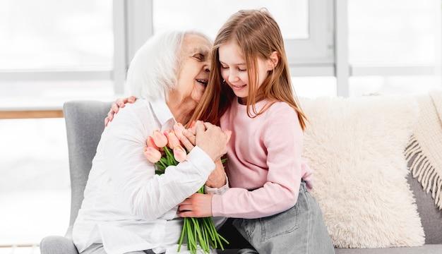 Kleindochter geeft bloemen tulpenboeket aan grootmoeder en knuffelt haar binnenshuis thuis
