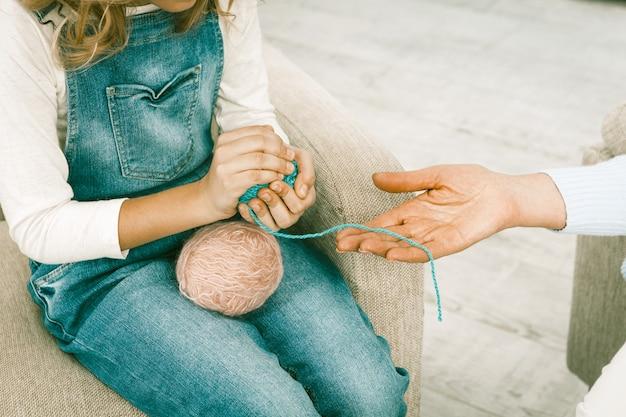 Kleindochter helpt haar grootmoeder om draad voor breien voor te bereiden