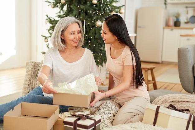 Kleindochter opent het kerstcadeau samen met haar grootmoeder en viert thuis kerstmis