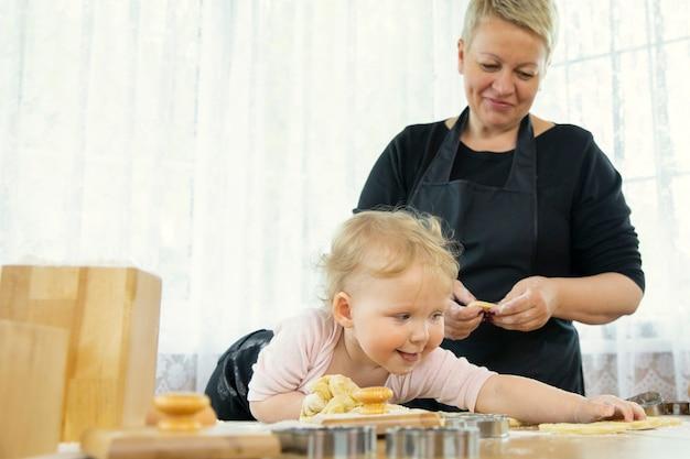 Kleindochter werd vies van bloem terwijl ze haar gelukkige grootmoeder hielp koekjes te maken
