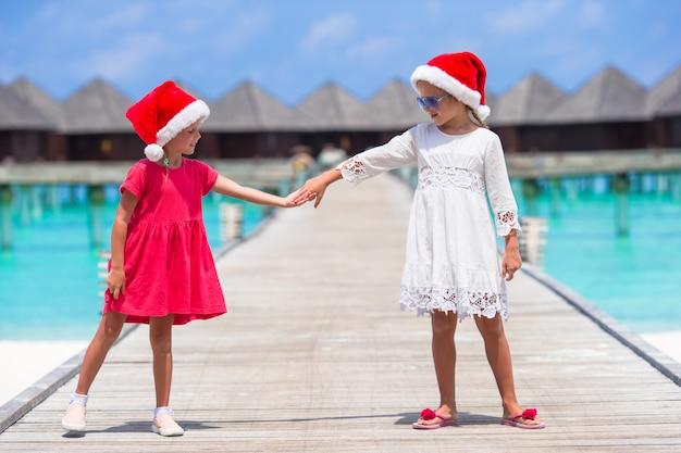 Kleine aanbiddelijke meisjes in kerstmanhoeden tijdens strandvakantie bij houten pier