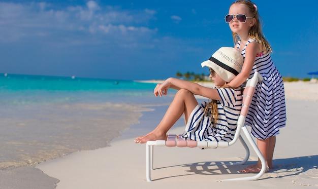 Kleine aanbiddelijke meisjes in ligstoel tijdens caraïbische vakantie