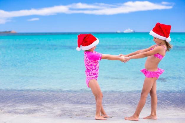 Kleine aanbiddelijke meisjes in rode kerstmanhoeden op strand tropische vakantie