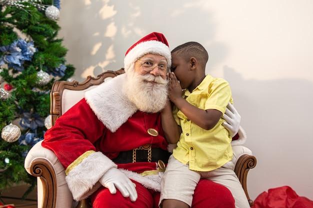 Kleine afrikaanse jongen die in het oor van de kerstman fluistert