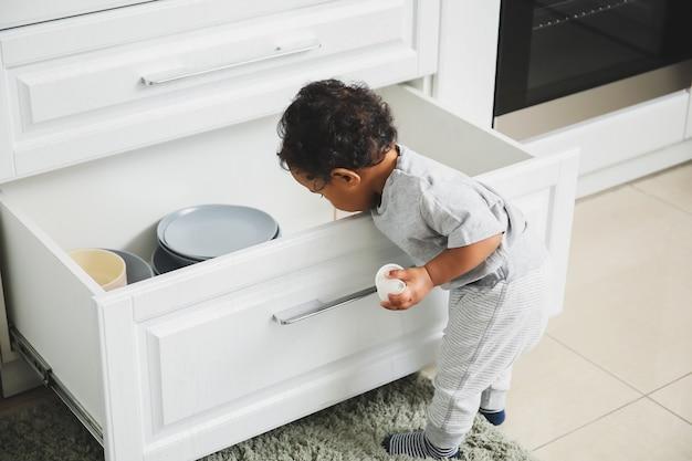 Kleine afro-amerikaanse baby spelen in de keuken. kind in gevaar