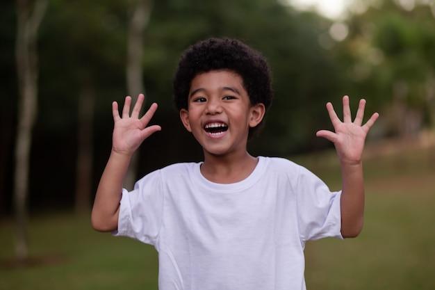 Kleine afrojongen die grimassen trekt en zijn handen naar de camera laat zien
