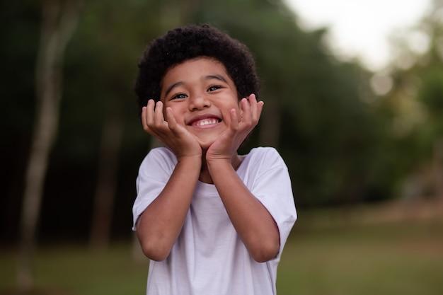 Kleine afrojongen die lacht naar de camera in het park