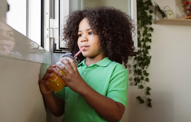 Kleine afrojongen drinkt sap met stro thuis bij het raam