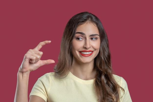 Kleine afstand. glimlachende jonge mooie vrouw met bruine ogen en lang donker haar die kleine afstand met vingers tonen