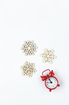 Kleine analoge rode klok, houten sneeuwvlokken op wit