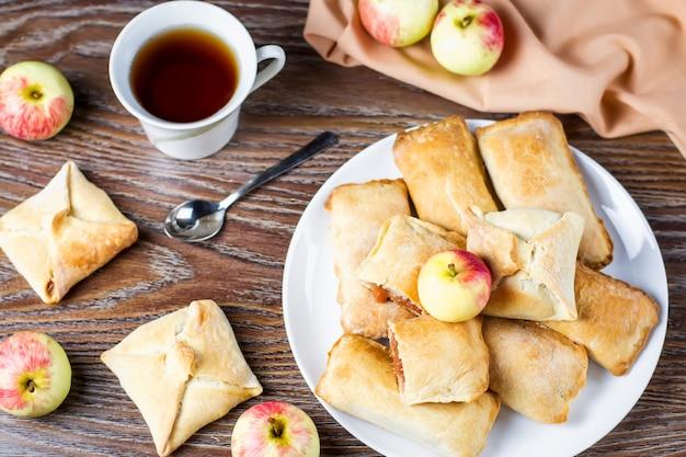 Kleine appeltaarten of appelflappen en kopje thee op houten tafel