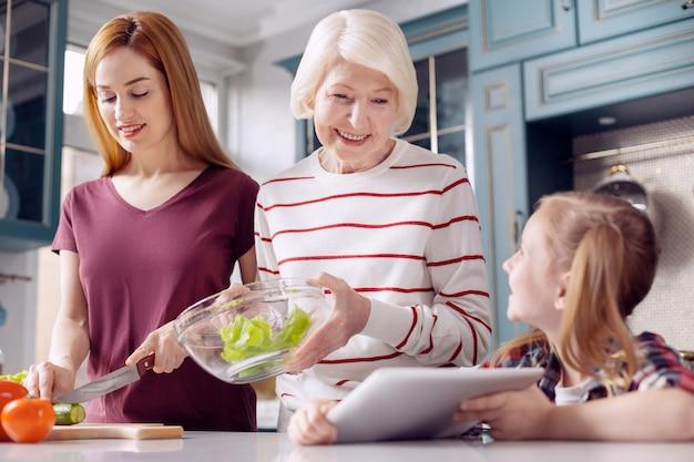 Kleine assistent. mooi klein meisje zit aan het aanrecht en toont een tablet met een recept aan haar moeder en grootmoeder terwijl de vrouwen salade maken