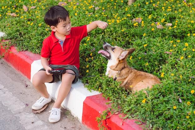 Kleine aziatische jongen en schattige hond in park
