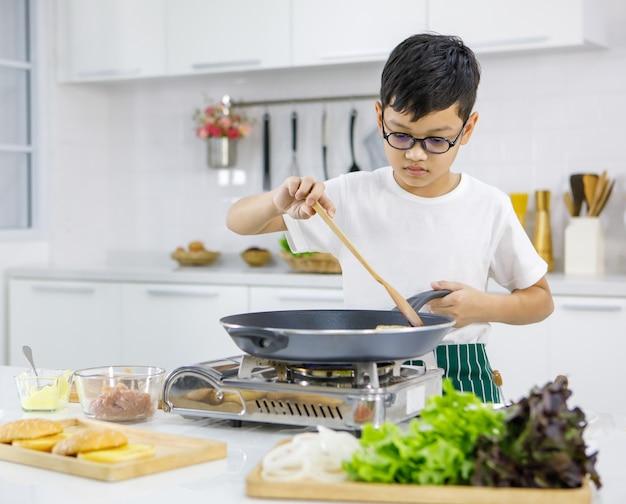 Kleine aziatische jongen in glazen die pasteitjes op hete pan bakken terwijl ze hamburgers bereiden voor de lunch in de moderne lichte keuken thuis. concept voor onderwijs en leren door te doen.