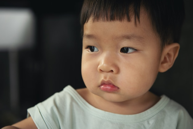 Kleine aziatische kinderen jongen steenbolk en frons op zwart.