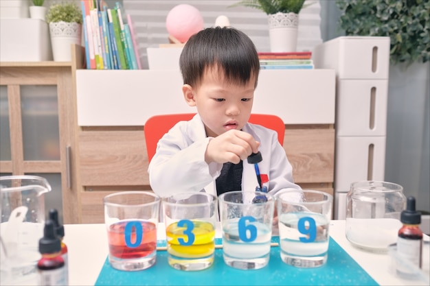 Kleine aziatische kleuterschool jongen studeren wetenschap