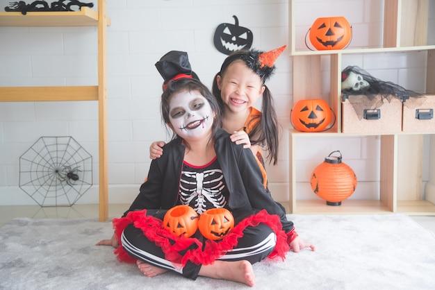 Kleine aziatische meisjes zitten en lachen in de kamer
