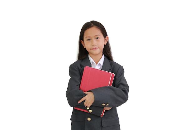 Kleine aziatische schoolmeisje in formele slijtage shirt, pak knuffelen een boek tijdens het kijken naar camera geïsoleerd op witte achtergrond.