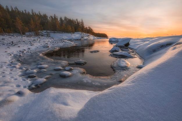 Kleine baai lake ladoga bij zonsopgang met verse sneeuw in de winter