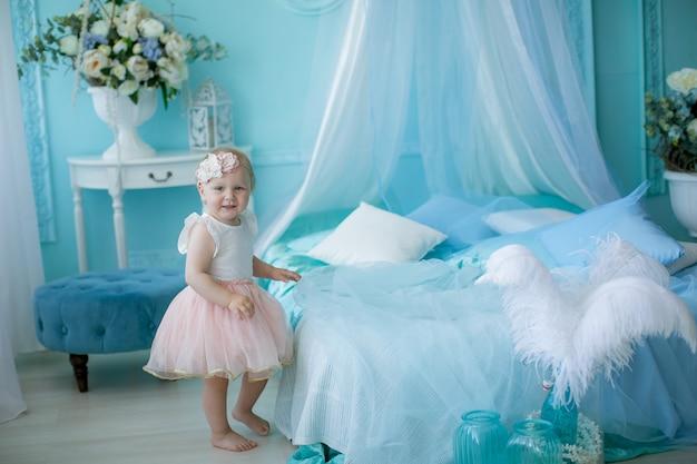Kleine baby 1 jaar vanaf de geboorte zittend op een bed of op een stoel in een lichtblauwe kinderkamer.