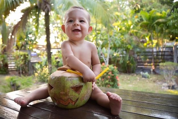 Kleine baby baby haalt stro uit groene kokosnoot die is gemaakt in de vorm van halloween-symbool