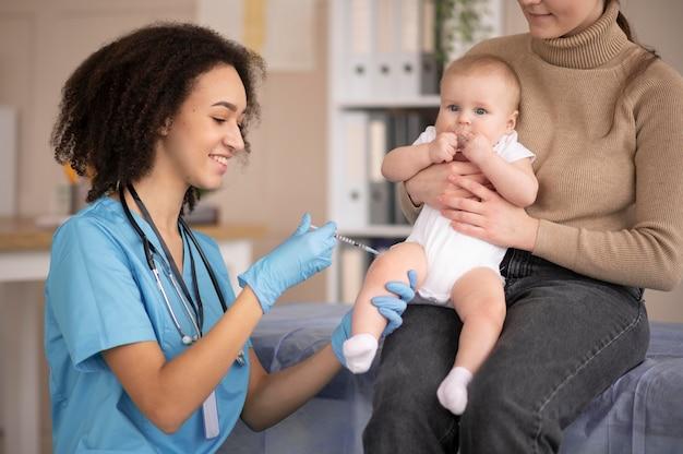 Kleine baby die bij de gezondheidskliniek is voor vaccinatie
