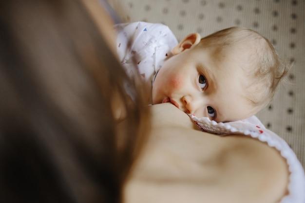 Kleine baby die moeders melk zuigt