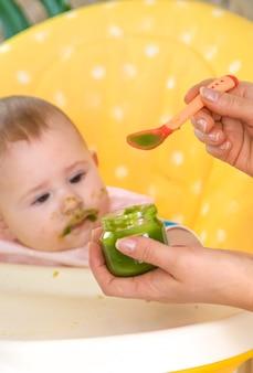 Kleine baby eet broccoli groentepuree. selectieve aandacht. mensen.