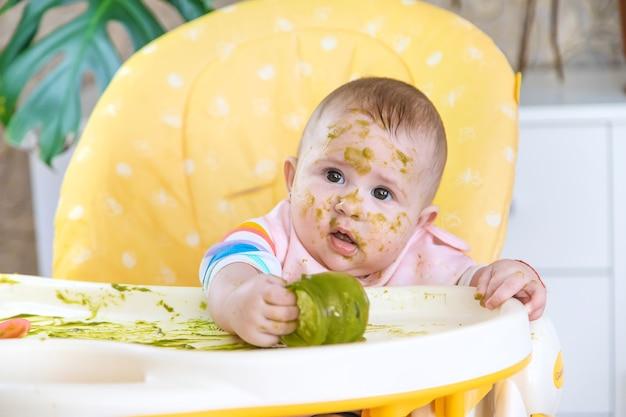 Kleine baby eet zelf broccolipuree. selectieve aandacht. mensen.