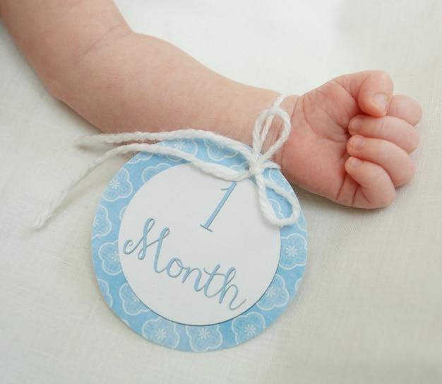 Kleine baby hand met zachte, tere huid geïsoleerd op een witte muur. tag met de woorden van 1 maand. gezonde een maand oud pasgeboren babyjongen liggend op het bed. de hand van het kleine kind close-up.