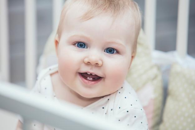 Kleine baby in de wieg werd 's ochtends wakker en lachte thuis