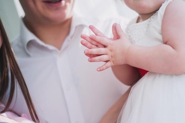 Kleine baby in een witte jurk handen klappen